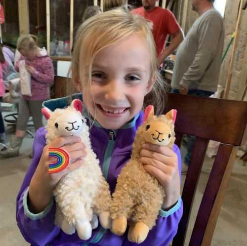 Natalie Holding Stuffed Alpaca Toys